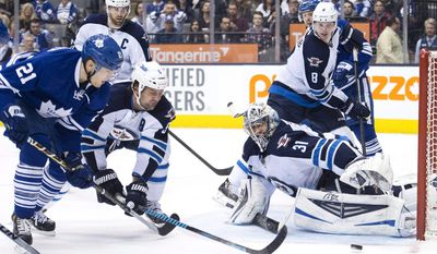 Winnipeg Jets goalie Ondrej Pavelec (31) makes a save as Toronto Maple Leafs forward James van Riemsdyk (21) and Jets defenseman Mark Stuart (5) battle for the loose puck during second-period NHL hockey game action in Toronto, Saturday, April 5, 2014. (AP Photo/The Canadian Press, Nathan Denette)