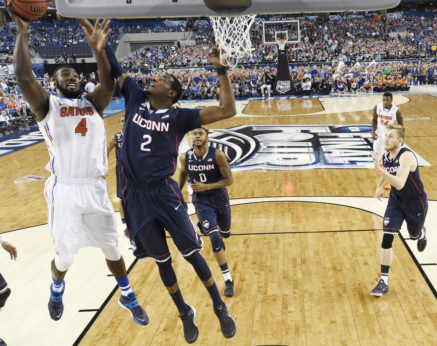 Florida center Patric Young (4) drives to the basket past Connecticut forward DeAndre Daniels (2) during the first half of the NCAA Final Four tournament college basketball semifinal game Saturday, April 5, 2014, in Dallas. (AP Photo/Chris Steppig, NCAA Photos)