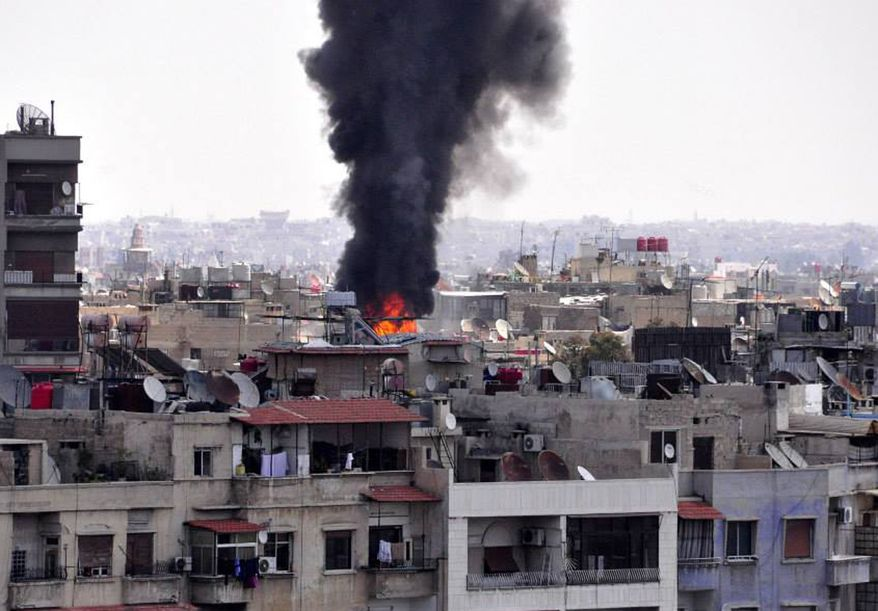 In this photo released by the Syrian official news agency SANA, black smoke and flame rise from the rooftop of a building that was, according to SANA, attacked by a mortar shelled by the Syrian rebels in Damascus, Syria, Saturday April 5, 2014. Al-Qaida's leader, Ayman al-Zawahri, called on fighters to determine who killed his chief representative in Syria, a man many militant groups believe died at the hands of a rival militia, in a move that highlighted a conflict between rebels that has killed hundreds. (AP Photo/SANA)