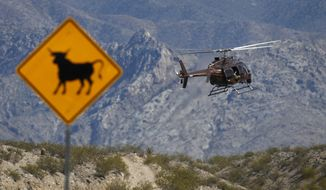 A helicopter takes off from a staging area of Bureau of Land Management vehicles and other government vehicles off of Riverside Road near Bunkerville, Nev., Saturday, April 5, 2014. (AP Photo/Las Vegas Review-Journal, John Locher)
