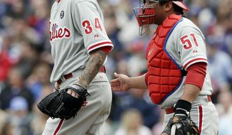 Philadelphia Phillies starter A.J. Burnett, left, talks with catcher Carlos Ruiz during the first inning of a baseball game against the Chicago Cubs in Chicago, Sunday, April 6, 2014. (AP Photo/Nam Y. Huh)