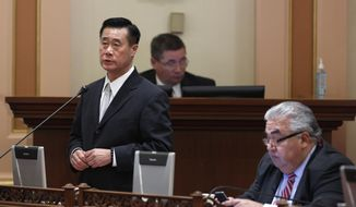 FILE -- In this Jan. 28, 2014 file photo, state Sen. Leland Yee, D-San Francisco, left, speaks on a bill, while his seat mate  Sen. Ron Calderon, D-Montebello, works at his desk at the Capitol  in Sacramento, Calif. In the wake the recent indictments of Yee and Calderon on federal corruption charges lawmakers are proposing to strengthen political ethics and reform campaign finance laws.(AP Photo/Rich Pedroncelli, file)