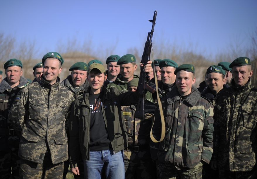 In this photo taken on Saturday, April  5, 2014, Oleh Lyashko, center left, leader of Ukrainian Radical Party and presidential candidate who supported the protests that ousted Russian-leaning president Viktor Yanukovych, poses with Ukrainian soldiers and officers at their camp near Ukraine-Russian border outside Chernihiv, 140km (87 miles) northeast of Kiev, Ukraine. Ukraine's security service said Saturday it has detained a 15-strong armed gang planning to seize power in an eastern province on the border with Russia. (AP Photo/Osman Karimov)