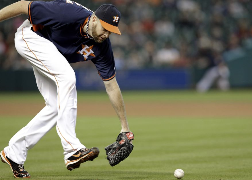 Houston Astros starting pitcher Scott Feldman cannot get to the ball in time, giving Los Angeles Angels' Josh Hamilton a single, in the fourth inning of a baseball game on Sunday, April 6, 2014, in Houston. (AP Photo/Pat Sullivan)