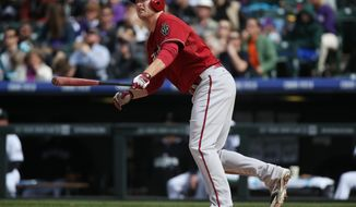 Arizona Diamondbacks' Mark Trumbo follows the flight of his two-run home run against the Colorado Rockies in the fifth inning of an MLB National League baseball game in Denver on Sunday, April 6, 2014. (AP Photo/David Zalubowski)