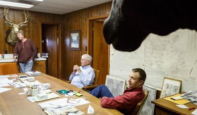 Stewart Savage, left, and his brother Kirby, right, sit with their father Harley in the Triangle Rice Farms office discussing the third consecutive year without irrigation water from the Colorado River for rice farmers in Matagorda County, Wednesday, March 19, 2014, in Bay City. (AP Photo/Houston Chronicle, Michael Paulsen)