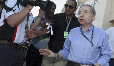 FIA president Jean Todt is embraced by a Ferrari gesticulates with reporters upon his arrival in the paddock after the third practice session at the Formula One Bahrain International Circuit in Sakhir, Bahrain, Saturday, April 5, 2014. The Bahrain Formula One Grand Prix will take place here on Sunday. (AP Photo/Luca Bruno)
