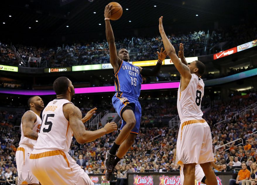 Oklahoma City Thunder guard Reggie Jackson (15) drives as Phoenix Suns' Channing Frye (8), Marcus Morris (15) and P.J. Tucker defend during the first half of an NBA basketball game on Sunday, April 6, 2014,in Phoenix. (AP Photo/Matt York)