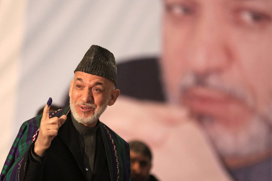 Not going anywhere: Afghan President Hamid Karzai shows indelible ink on his finger before he casts his vote. Zalmay Rassoul has the backing of Mr. Karzai's clan and political machinery.