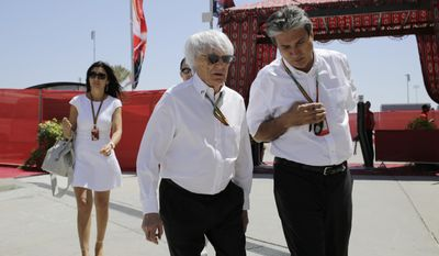 President and CEO of Formula One Management Bernie Ecclestone, center, and his partner Fabiana Flosi, left, walk in the paddock ahead of the Bahrain Formula One Grand Prix at the Formula One Bahrain International Circuit in Sakhir, Bahrain, Sunday, April 6, 2014. (AP Photo/Hassan Ammar)