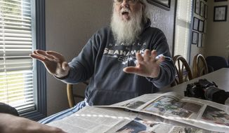 This March 31, 2014 photo shows Larry Taylor who survived the Oso mudslide, talks about the moments after the landslide hit and the photos he took of the helicopter rescue that took place near his home, in Arlington, Wash.  (AP Photo/The Seattle Times, Steve Ringman) SEATTLE OUT; USA TODAY OUT; MAGS OUT; TELEVISION OUT; NO SALES; MANDATORY CREDIT TO BOTH THE SEATTLE TIMES AND THE PHOTOGRAPHER