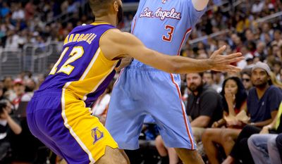 Los Angeles Lakers guard Kendall Marshall (12) pressures Los Angeles Clippers guard Chris Paul (3) who looks for an open man in the first half of an NBA basketball game on Sunday, April 6, 2014, in Los Angeles. (AP Photo/Gus Ruelas)