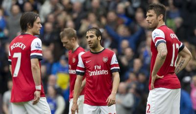 Arsenal's Mathieu Flamini, centre, stands amongst teammates as they wait for play to restart after Everton's second goal during their English Premier League soccer match at Goodison Park Stadium, Liverpool, England, Sunday April 6, 2014. (AP Photo/Jon Super)