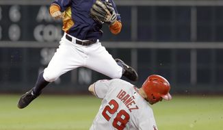 Houston Astros second baseman Jose Altuve, top, jumps over Los Angeles Angels' Raul Ibanez (28) to watch his throw be too late to complete the double play on Angels' Howie Kendrick in the seventh inning of a baseball game on Sunday, April 6, 2014, in Houston. (AP Photo/Pat Sullivan)