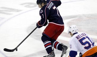Columbus Blue Jackets' Jack Johnson, left, controls the puck against New York Islanders' Frans Nielsen, of Denmark,  in the third period of an NHL hockey game in Columbus, Ohio, Sunday, April 6, 2014. The Blue Jackets won 4-0. (AP Photo/Paul Vernon)