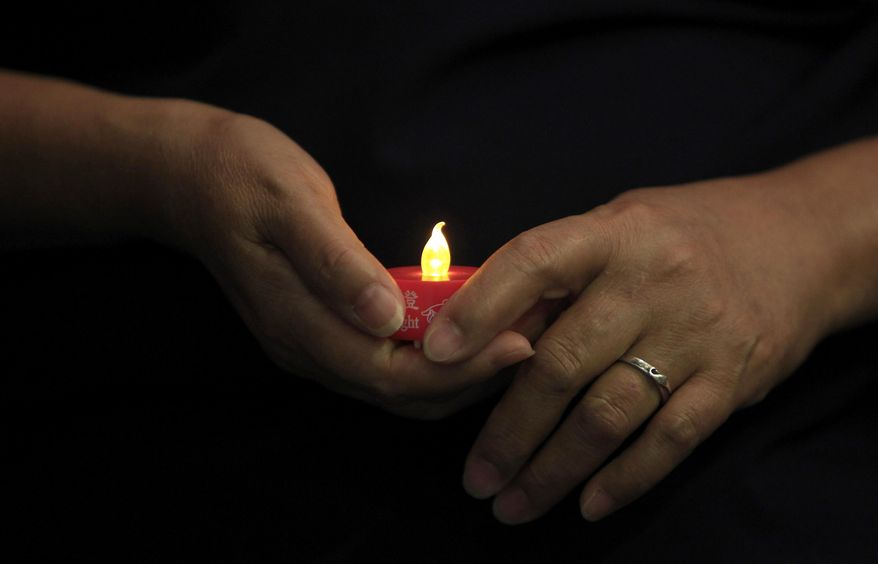 A woman holds an LED candle as she offers prayers during a mass prayer for the missing Malaysia Airlines Flight 370, in Kuala Lumpur, Malaysia, Sunday, April 6, 2014. The head of the multinational search for the missing Malaysia airlines jet said that electronic pulses reportedly picked up by a Chinese ship are an encouraging sign but stresses they are not yet verified. (AP Photo/Lai Seng Sin)