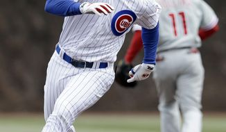 Chicago Cubs' Ryan Kalish runs to third after hitting a triple during the first inning of a baseball game scoring Emilio Bonifacio against the Philadelphia Phillies in Chicago, Sunday, April 6, 2014. (AP Photo/Nam Y. Huh)