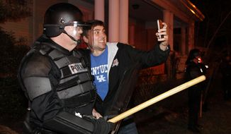 Eastern Kentucky University junior Eric Kuertz, right, takes a selfie with UK Police officer Lt. Greg Hall as Kentucky fans react to their teams semi-final victory on State St., near the University of Kentucky campus, Saturday, April 5, 2014, in Lexington, Ky. The win advances the Wildcats to the championship game of the NCAA men's college basketball tournament. (AP Photo/James Crisp)