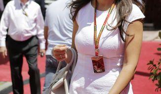 Fabiana Flosi partner of Bernie Ecclestone, left, president and CEO of Formula One Managmen walks at the paddock ahead of the Bahrain Formula One Grand Prix at the Formula One Bahrain International Circuit in Sakhir, Bahrain, Sunday, April 6, 2014. (AP Photo/Hassan Ammar)