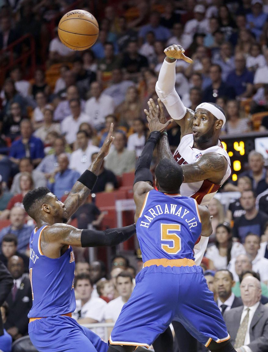Miami Heat forward LeBron James passes past New York Knicks guard Iman Shumpert, left, and guard Tim Hardaway Jr. (5) during the first half of an NBA basketball game, Sunday, April 6, 2014, in Miami. (AP Photo/Wilfredo Lee)