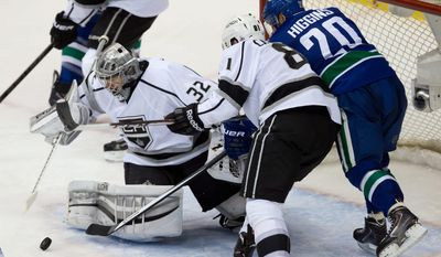 Vancouver Canucks' Chris Higgins, right, is checked by Los Angeles Kings' Andrew Campbell, center, as goalie Jonathan Quick corrals the puck during the second period of an NHL hockey game Saturday, April 5, 2014, in Vancouver, British Columbia. (AP Photo/The Canadian Press, Darryl Dyck)