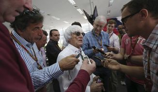 Bernie Ecclestone, center, president and CEO of Formula One Management, center, answers to reporters in the newsroom ahead the the Bahrain Formula One Grand Prix at the Bahrain International Circuit in Sakhir, Bahrain, Sunday, April 6, 2014. (AP Photo/Luca Bruno)
