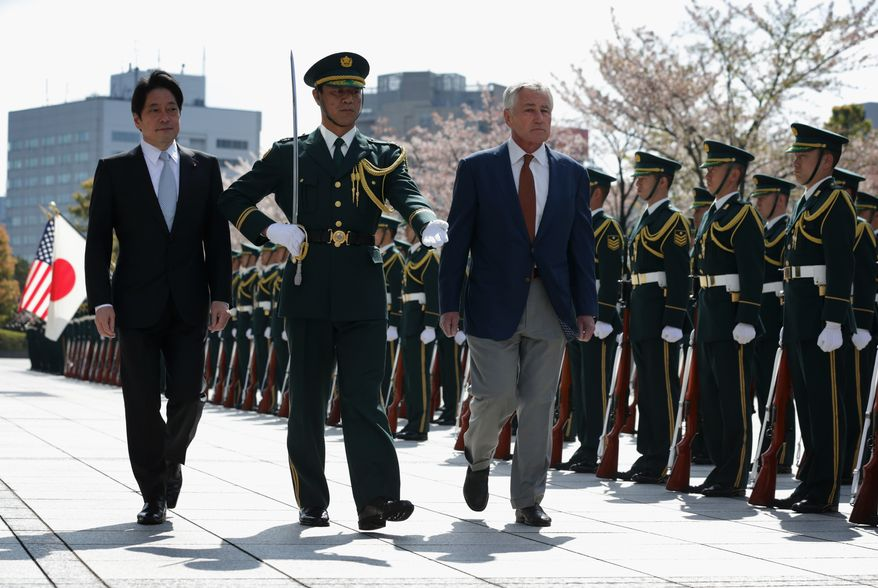 Accompanied by Japanese Defense Minister Itsunori Onodera, left, U.S. Secretary of Defense Chuck Hagel, right, reviews honor guards at the Japanese Ministry of Defense headquarters April 6, 2014 in Tokyo, Japan. Secretary Hagel is visiting Japan, China and Mongolia. It is his fourth trip to Asian nations since taking office.  (AP Photo/Alex Wong, POOL)