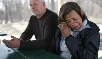 Shirley Bak, right, wipes a tear as she speaks with a reporter about her son Travis Benjamin, the 39-year-old who went missing after his Hummer went into the Mississippi River early Friday, April 4, 2014, in Ramsey. At right is Clemons Bak, Benjamin's stepfather.   (AP Photo/Star Tribune, David Denney)