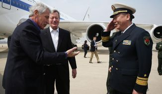 U.S. Secretary of Defense Chuck Hagel, left, is welcomed by Rear Admiral Guan Youfei, Director of Foreign Affairs Office of the Chinese Defense Ministry and U.S. Ambassador to China, Max Baucus, upon his arrival at Qingdao International Airport in Qingdao, China, Monday, April 7, 2014. Hagel is currently on his fourth trip to Asian nations since taking office. (AP Photo/Alex Wong, Pool)
