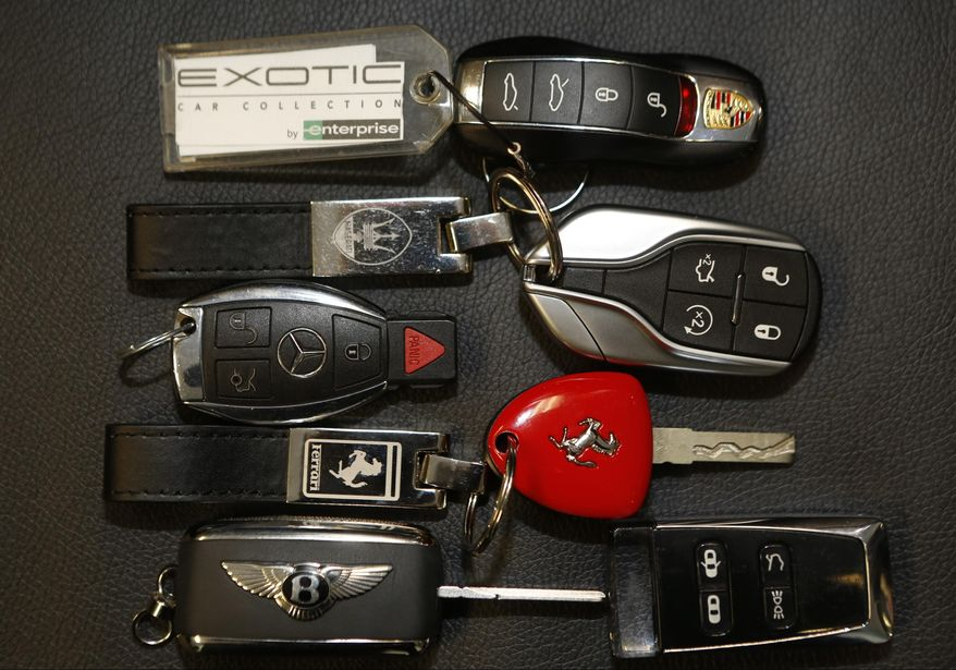 In this Wednesday, March, 26, 2014 photo, luxury car keys for Porsche, Maserati, Jaguar, Mercedes-Benz, Ferrari, Bentley Continental, and Aston Martin are displayed at the Enterprise Exotic Car Collection showroom near Los Angeles International Airport. (AP Photo/Damian Dovarganes)