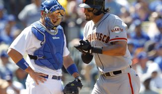 Los Angeles Dodgers catcher A.J. Ellis, left, watches as San Francisco Giants' Michael Morse, right, applauds at home plate after hitting a solo home run in the fourth inning in a baseball game on Saturday, April 5, 2014, in Los Angeles. (AP Photo/Alex Gallardo)