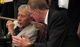 Kansas state Reps. Shanti Gandhi, left, a Topeka Republican, and David Crum, an Augusta Republican, confer during the House's debate on a school funding plan, Sunday, April 6, 2014, at the Statehouse in Topeka, Kan. The plan boosts aid to poor school districts but eliminates tenure for public school teachers. (AP Photo/John Hanna)