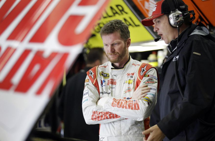 Dale Earnhardt Jr., left, talks with his crew chief Steve Letarte in the garage during a practice session for the NASCAR Sprint Cup Series auto race at Texas Motor Speedway in Fort Worth, Texas, Saturday, April 5, 2014. (AP Photo/LM Otero)