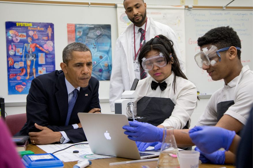 """President Obama looks over students' work as he visits a classroom at Bladensburg High School on Monday. At Bladensburg, the Obama administration unveiled the $107 million Youth CareerConnect program designed to """"deliver real-world learning opportunities for students"""" and offer specific training in a given field before a student graduates high school. (Associated Press)"""