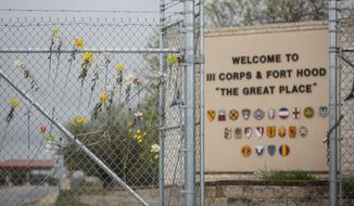 In this file photo, flowers decorate a fence outside of Fort Hood's east gate on Sunday, April 6, 2014, in Killeen, Texas, in honor of those killed and wounded in the Fort Hood shooting on April 2.  (AP Photo/ Tamir Kalifa) **FILE**