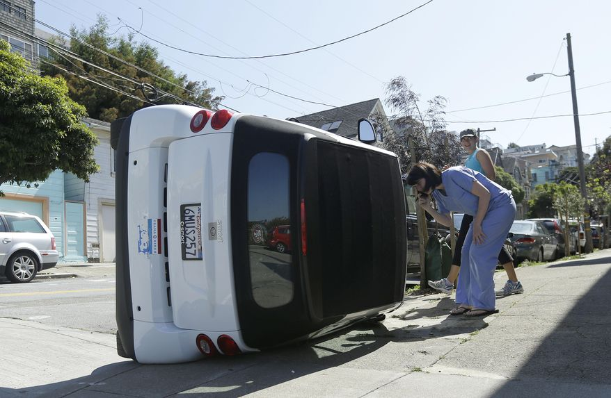 Shelley Gallivan, foreground right, looks into a tipped over Smart car which belongs to her friend on the corner of Prospect and Oso streets in San Francisco, Monday, April 7, 2014. Police in San Francisco are investigating why four Smart cars were flipped over during an apparent early morning vandalism spree. Officer Gordon Shyy, a police spokesman, says the first car was found flipped on its roof and a second was spotted on its side around 1 a.m. Monday in the Bernal Heights neighborhood. (AP Photo/Jeff Chiu)