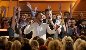 Luke Bryan, left, and Blake Shelton take a selfie in the audience at the 49th annual Academy of Country Music Awards at the MGM Grand Garden Arena on Sunday, April 6, 2014, in Las Vegas. (Photo by Chris Pizzello/Invision/AP)