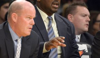 FILE - In this Nov. 9, 2012, file photo, Los Angeles Lakers assistant coaches Steve Clifford, left, and Chuck Person sit on the bench during the first half of an NBA basketball game against the Golden State Warriors in Los Angeles. Former Auburn All-American and NBA player Person is returning to the school as an assistant coach. New Tigers coach Bruce Pearl announced the hiring of the program's top scorer on Monday, April 7, 2014. (AP Photo/Mark J. Terrill, File)