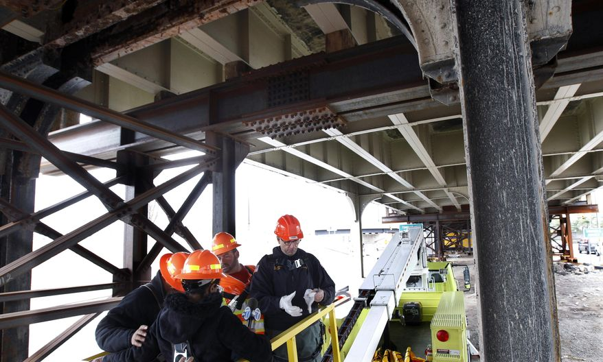 A network of temporary support beams, left, are seen as James S. Simpson right, commissioner of New Jersey's Department of Transportation, and others use a lift to examine the underside of the road surface of the Pulaski Skyway Monday, April 7, 2014, in Jersey City, N.J. The 81-year-old span will be closed for a major makeover that will take two years, beginning this Saturday. The project will require the closure of northbound lanes that feed into Jersey City and the Holland Tunnel. The DOT estimates about 40,000 vehicles use the inbound span each day, including about 10,000 during the morning commute. (AP Photo/Mel Evans)
