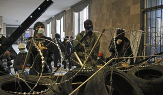 Activists prepare a barricade inside the regional administration building in Donetsk, Ukraine, Monday, April 7, 2014. A Ukrainian news agency is reporting that pro-Russian separatists who have seized the regional administration building in the eastern Ukrainian city of Donetsk proclaimed the region an independent republic. (AP Photo/Alexander Ermochenko)