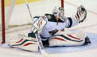 Minnesota Wild's Ilya Bryzgalov (30) makes a quick glove save against the Winnipeg Jets' during first period NHL hockey action in Winnipeg, Manitoba, Monday, April 7, 2014. (AP Photo/The Canadian Press, Trevor Hagan)