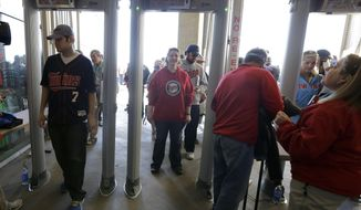 Fans enter Target Field through newly installed metal detectors before the Minnesota Twins host the Oakland Athletics in a home opener baseball game in Minneapolis, Monday, April 7, 2014.  Only a few of the gates currently have metal detectors, but they will be installed at each gate before Minneapolis hosts the All Star Game in July. (AP Photo/Ann Heisenfelt)