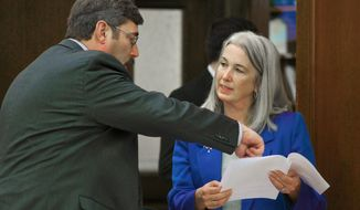 Rep. Cathy Munoz, R-Juneau, speaks with Rep. Eric Feige, R-Chickaloon, on the House floor at the Capitol in Juneau, Alaska, on Friday, April 4, 2014. (AP Photo/Juneau Empire, Michael Penn)