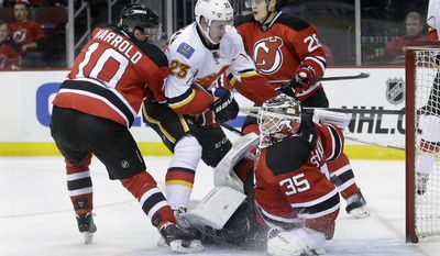 Calgary Flames Sean Monahan (23) gets between New Jersey Devils Peter Harrold (10) and Anton Volchenkov (28), of Russia,  as  Devils goalie Cory Schneider (35) stretches to protect the net during the first period of an NHL hockey game in Newark, N.J., Monday, April 7, 2014. (AP Photo/Mel Evans)