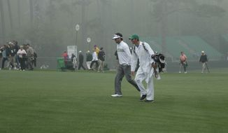 "Bubba Watson and his caddie walk past the location where the 65-feet high Eisenhower Tree was located on the 17th fairway during a practice session for the Masters golf tournament Monday, April 7, 2014, in Augusta, Ga. The Eisenhower Tree was recently removed after a winter storm in February ""caused irreparable damage"" to many of its branches. (AP Photo/Charlie Riedel)"