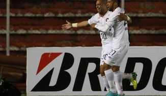 Adriano of Brazil's Atletico Paranaense, left, celebrates with teammate Matias Mirabaje after scoring against Bolivia's The Strongest at a Copa Libertadores soccer match in La Paz, Bolivia, Tuesday, April 8, 2014. (AP Photo/Juan Karita)