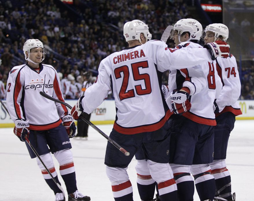 Washington Capitals' Alex Ovechkin (8) is congratulated by teammates Jason Chimera (25), John Carlson (74) and Mike Green (52) after he scored his 50th goal of the season, during the first period of an NHL hockey game against the St. Louis Blues, Tuesday, April 8, 2014 in St. Louis.(AP Photo/Tom Gannam)