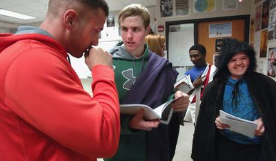 """In this March 20, 2014 photo, English teacher Brad Bovenkerk, left, helps Jack Kestian, who plays Caesar, and Emily Henrichs, who plays a soothsayer, with their lines as students prepare to perform Shakespeare's """"Julius Caesar"""" at Normal Community High School in Normal, Ill. (AP Photo/The Pantagraph, David Proeber)"""
