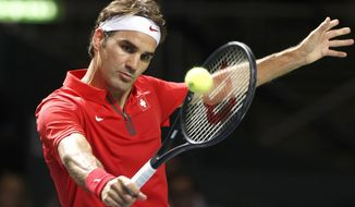 Switzerland's Roger Federer, returns a ball to Andrey Golubev, of Kazakhstan, during the fourth tennis single match of the Davis Cup World Group Quarterfinal match between Switzerland and Kazakhstan, at Palexpo, in Geneva, Switzerland, Sunday, April 6, 2014.  Federer won the decisive singles match on Sunday to give Switzerland a 3-2 win over Kazakhstan in the Davis Cup and a spot in the semifinals for the first time in 11 years. (AP Photo / Keystone, Salvatore Di Nolfi)