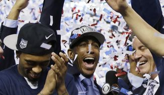 Connecticut head coach Kevin Ollie, center, celebrates with his team after their 60-54 victory over Kentucky in the NCAA Final Four tournament college basketball championship game Monday, April 7, 2014, in Arlington, Texas. (AP Photo/David J. Phillip)